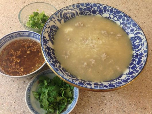 Thailand's rice porridge, kao tome, with chopped green onions, chopped cilantro, and crispy garlic in oil